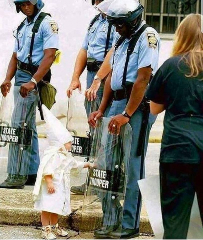 """A child identified only as Josh plays with the shield of a Georgia State Patrol trooper during Saturday's Ku Klux Klan march in Gainesville"" - original caption of Todd Robertson's photo 1992.jpg"